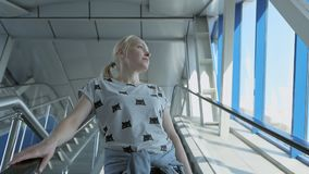 A woman goes down the escalator in a business center or airport. A woman dressed in casual clothes goes down the escalator in a business center or airport stock video