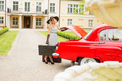 Woman dressed in cocktail dress holding vintage suitcase. Next to red retro car Stock Photography