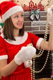 Woman dressed costume Santa Claus by fireplace. Christmas Royalty Free Stock Images
