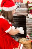Woman dressed costume Santa Claus by fireplace. Christmas Royalty Free Stock Photography