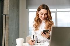 Woman dressed in formal clothes shirt indoors using mobile phone writing notes royalty free stock photos