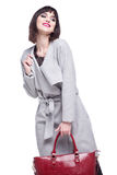 Woman dressed in a gray coat, beautiful smiles. Young woman dressed in a gray coat, beautiful smiles Royalty Free Stock Photography