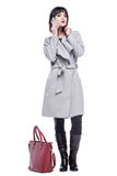 Woman dressed in a gray coat talking on the phone. Young woman dressed in a gray coat talking on the phone Stock Images