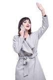 Woman dressed in a gray coat waving talking on the phone. Beautiful woman dressed in a gray coat waving talking on the phone Stock Photo