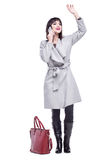 Woman dressed in a gray coat waving talking on the phone. Beautiful woman dressed in a gray coat waving talking on the phone Royalty Free Stock Images