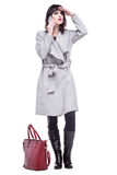 Woman dressed in a gray coat waving talking on the phone. Beautiful woman dressed in a gray coat waving talking on the phone Stock Images