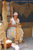 A woman dressed in medieval attire spins wool. During the Burgfest medieval festival in Burghausen,Germany Royalty Free Stock Images