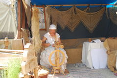 A woman dressed in medieval attire spins wool. During the Burgfest medieval festival in Burghausen,Germany Stock Images