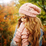 Woman dressed in pink knitted hat and gloves. Sunny autumn portrait of a cute young woman dressed in pink knitted hat and gloves Royalty Free Stock Photos