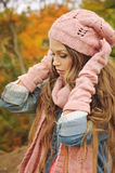 Woman dressed in pink knitted hat, scarf and gloves in autumn park. Stock Images