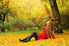 Woman dressed in red coat relaxing in autumn park. Stock Photography