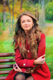 Woman dressed in red coat sitting in autumn park. Stock Photography