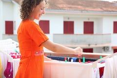 Woman dressed in red dress hangs clean wear. Beautiful young woman dressed in red dress hangs clean wear on balcony Royalty Free Stock Photo