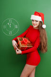 Woman dressed in red dress and santa hat with a pres Stock Photos