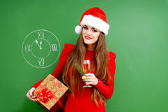Woman dressed in red dress and santa hat with a pres Stock Photography