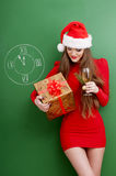 Woman dressed in red dress and santa hat with a present. Royalty Free Stock Photo
