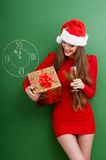 Woman dressed in red dress and santa hat Stock Images