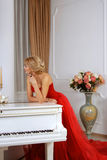 A woman dressed in red long dress leaning over white piano in th. Ought against a backdrop of bright colors Stock Images