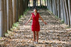 Woman dressed in red, meditating in the forest Stock Photo
