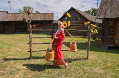 A woman dressed in Russian folk costume, standing with a yoke at the rustic fence. royalty free stock image