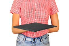 Woman dressed in shirt holding a square slate platter or a board in front of her. perspective view Template for your design. isola royalty free stock images