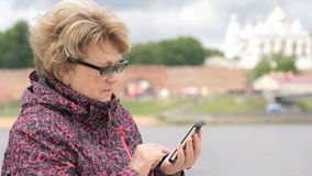 Woman dressed in sport jacket holding mobile phone stock footage