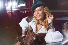 Woman dressed in steampunk style posing over retro car Royalty Free Stock Image
