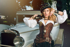 Woman dressed in steampunk style posing over retro car Royalty Free Stock Photography