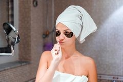 Woman dressed in a towel to brush her teeth in front of a mirror in the bathroom. healty wellness morning concept stock photo