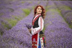 Bulgarian girl in a lavender field. Woman dressed in traditional bulgarian dress called Nosia enjoying a walk in a lavender field royalty free stock photo