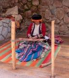A Woman Weaving Fibre Wool From Alpacas. A Woman, Dressed in Traditional Peruvian Attire, Weaving Fibre Wool From Alpacas royalty free stock photo