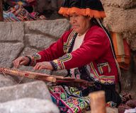 A Woman Weaving Fibre Wool From Alpacas. A Woman, Dressed in Traditional Peruvian Attire, Weaving Fibre Wool From Alpacas stock photography