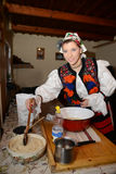Woman dressed in traditional romanian costume. Woman dressed in traditional clothes preparing to make a sponge cake for Christmas. The photo is taken in royalty free stock images
