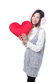 Woman dressed in warm clothes with love pillow Stock Photos