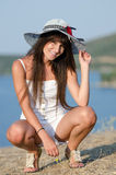 Woman dressed with white coveralls rompers joying the sunny day. Woman dressed with white coveralls rompers and packable floppy straw sun hat, joying the sunny Royalty Free Stock Images