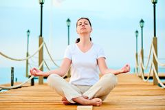 Woman dressed in white doing yoga Stock Image