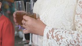 Woman holds two glasses of champagne. Close-up. Woman dressed in white dress stands at entrance to banquet hall of restaurant and holds two glasses of champagne stock video