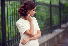 Woman dressed in white shirt in park on green natural background. Blurred background. Outdoor photo. Beauty and naturality Stock Image