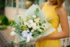 Woman dressed in a yellow dress holding a white bouquet of flowe. Rs on the blurred outdoors background Royalty Free Stock Image