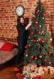 A woman dresses a Christmas tree Royalty Free Stock Image