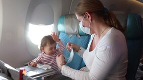 Woman dresses in a protective face gauze bandage on an airplane. Trying to put on a mask on a child. He resists. Protection