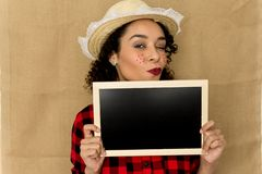 Woman dressing checked pattern clothes on rustic background. Funny Brazilian girl wearing red plaid shirt showing black board stock images