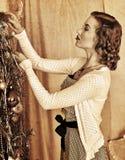 Woman dressing Christmas tree Stock Photos