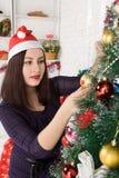 Woman dressing Christmas tree Royalty Free Stock Image