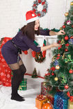 Woman dressing Christmas tree Royalty Free Stock Photos