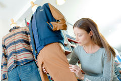 Woman dressing dummy in clothes shop. Woman dressing a dummy in a clothes shop Royalty Free Stock Images