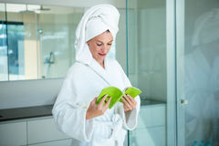 woman in a dressing gown reading a book Royalty Free Stock Photo