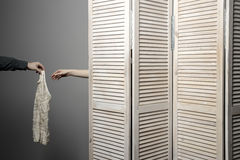 Woman in dressing room stall, the man's hand submits dress Stock Images