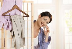 Woman dressing up and talking on mobile Stock Image