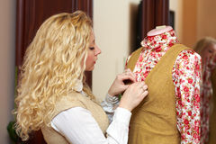 Woman, dressmaker working with mannequin at home. Portrait of woman, fashion designer, dressmaker working with tailoring mannequin at home studio Stock Photo